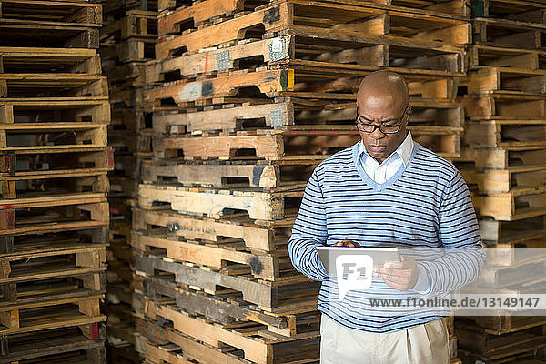 Male warehouse manager using digital tablet  pallets in background