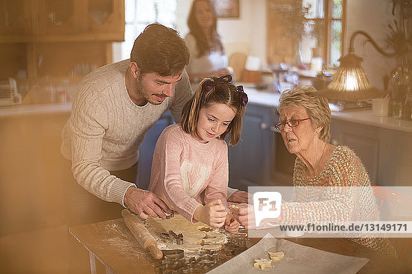 Three generation family cutting shapes in dough to make homemade cookies