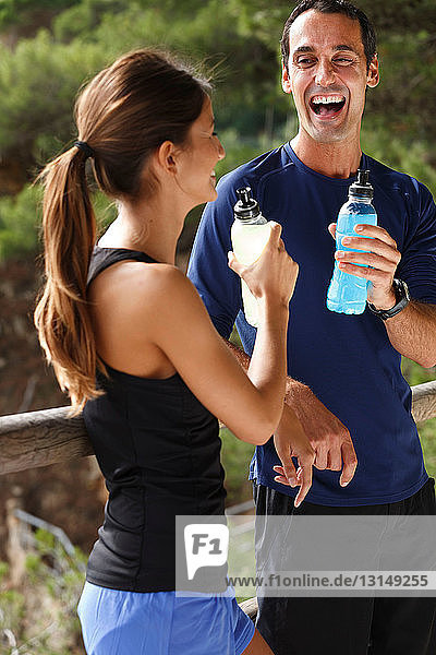 Couple drinking water outdoors
