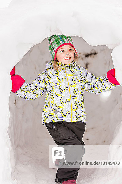Girl wearing winter clothes standing in igloo