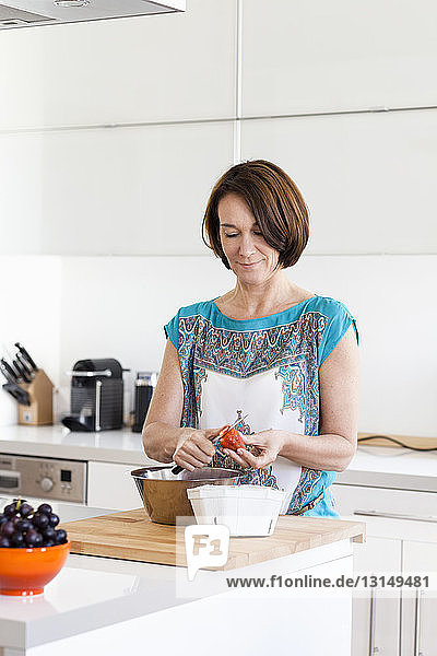 Mature woman preparing strawberries in apartment kitchen