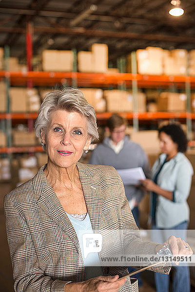 Female warehouse manager holding clipboard
