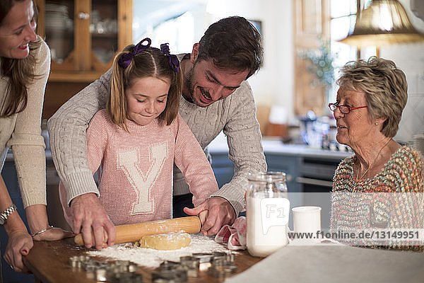 Father and daughter rolling dough to make homemade cookies