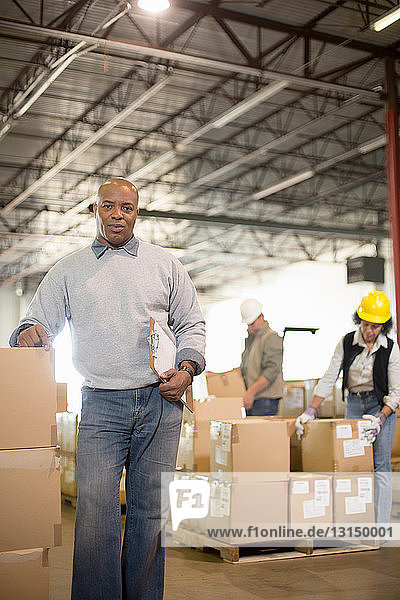 Portrait of male warehouse worker leaning on boxes