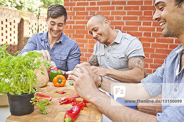 Three male friends laughing and preparing food for garden barbecue