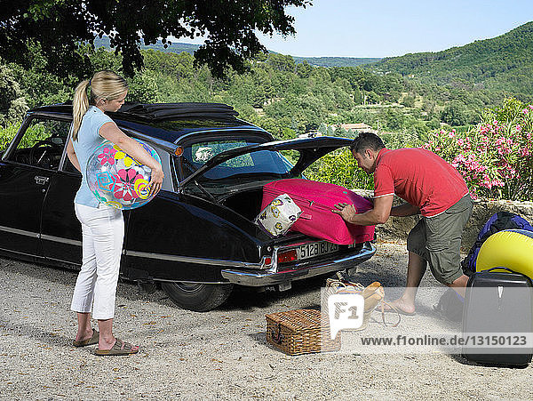 Woman watching man loading car