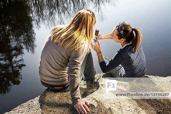 Two women looking at phone outdoors