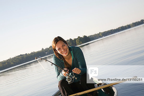 Woman fishing from canoe