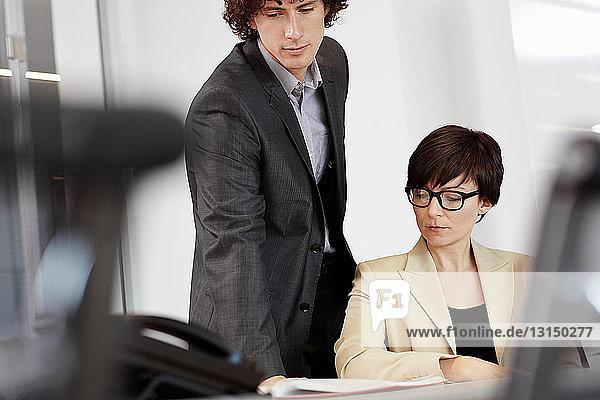Businesswoman sitting at desk  man looking over her shoulder at paperwork