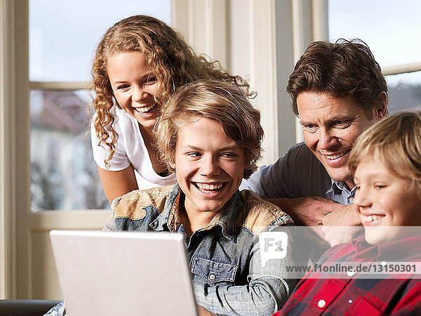 Father watching laptop with sons and daughter on sofa
