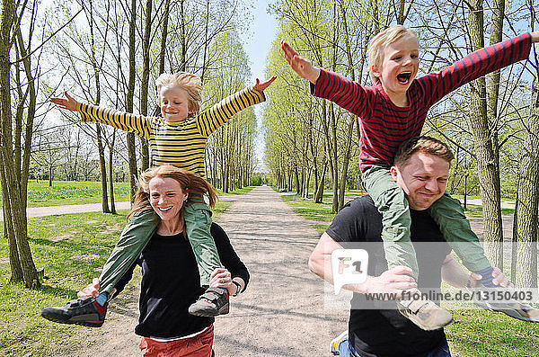Mother and father racing with two boys on shoulders through park