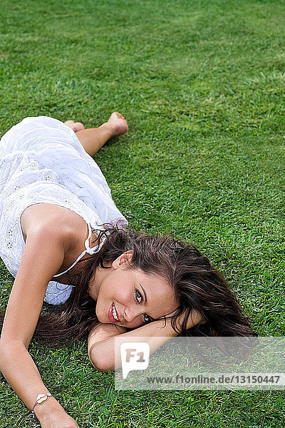 Young woman lays in grass