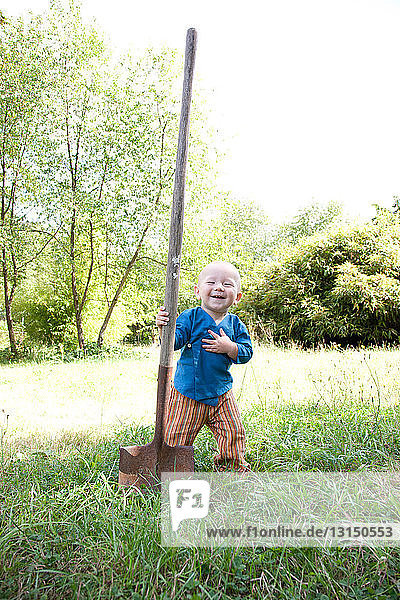 Toddler with big shovel in garden