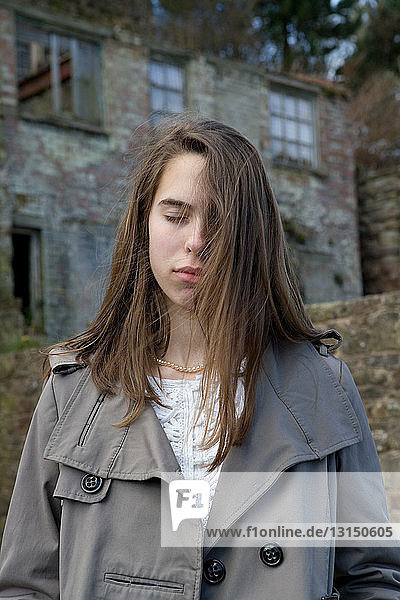 Teenage girl with eyes closed in front of derelict building