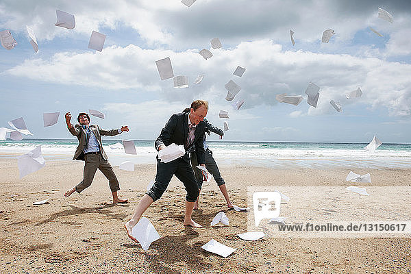 Businessmen tossing papers away at beach