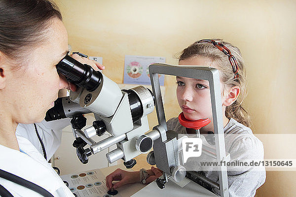 Optometrist examining girl's eyes