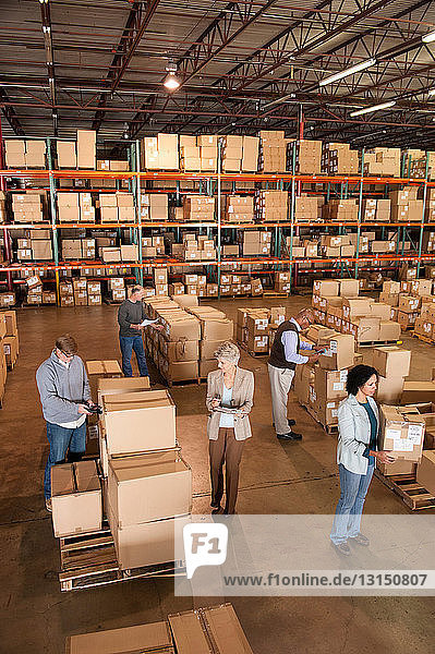 Warehouse workers standing with boxes  high angle