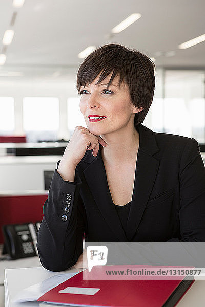 Businesswoman with hand on chin