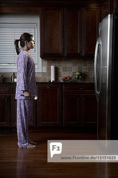 Woman in pyjamas  looking at refrigerator