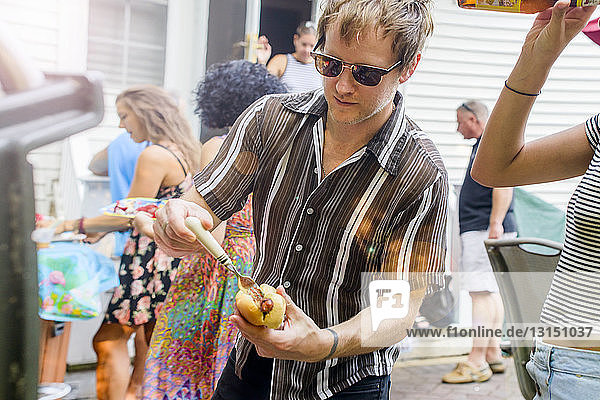 Mid adult man preparing hotdog at barbecue party in garden