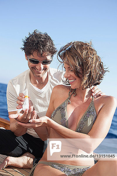couple laughing applying suntan lotion