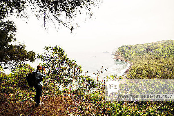 Mid adult man photographing coastline