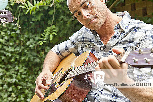 Mid adult man playing acoustic guitar in garden