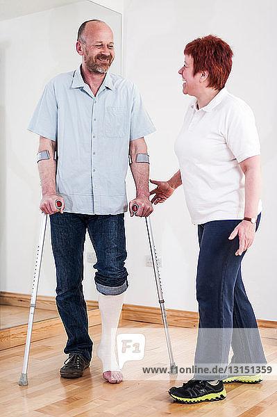 Man using crutches talking to woman