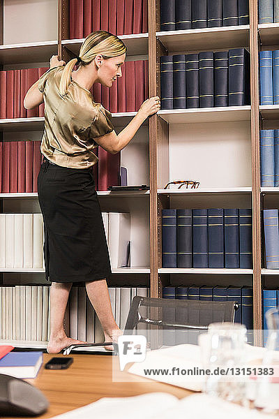 Female lawyer choosing books from bookcase