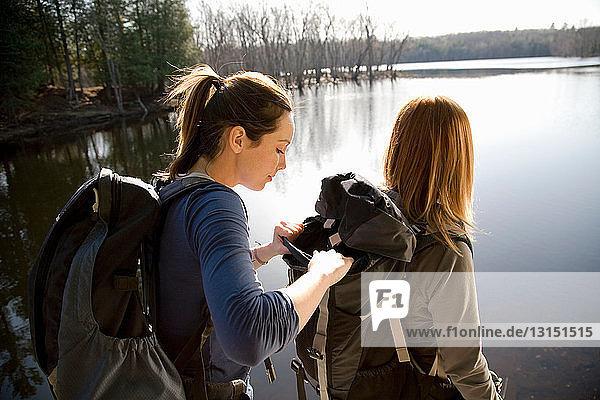 Two women hiking beside lake Two women hiking beside lake