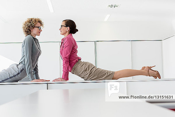 Two women lying on desk face to face