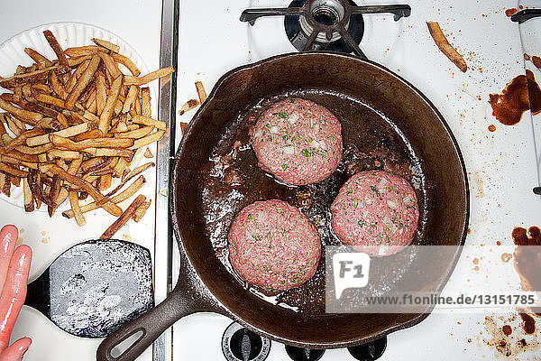 Burgers cooking in a frying pan