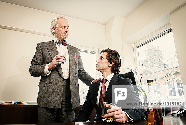 Two men drinking spirits in office