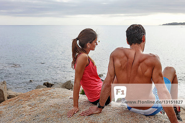 Couple on boulder overlooking ocean
