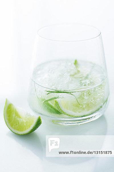 Glas Wasser mit Kalk und Kräutern