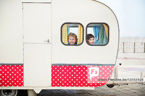 Boys looking through caravan windows  portrait