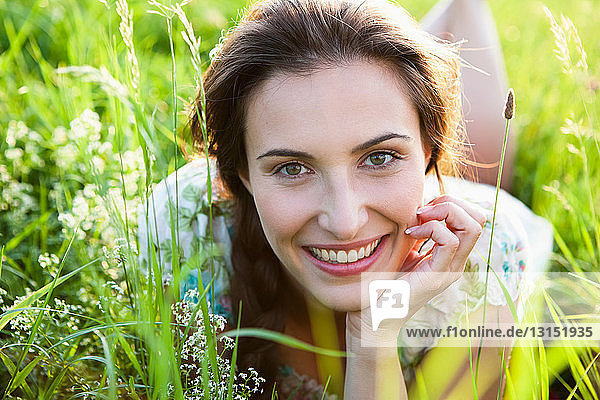 Smiling woman laying in tall grass