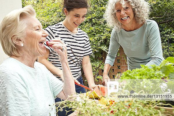 Three women preparing food at garden table