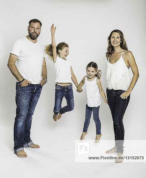 Studio portrait of two sisters jumping mid air between parents