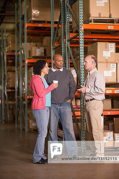 Warehouse workers standing by shelves with boxes