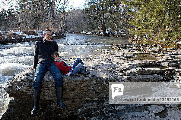 Father and son sitting on rocks by river