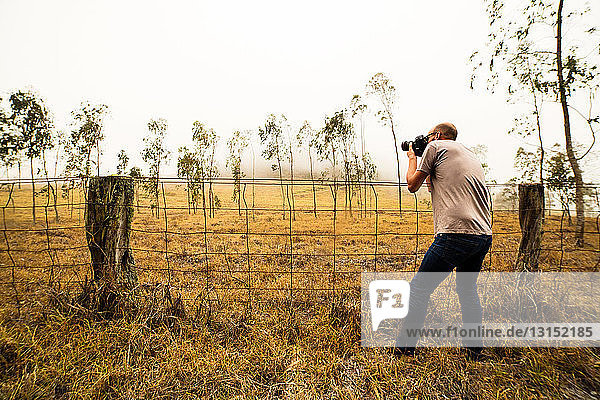 Mid adult man photographing field of saplings