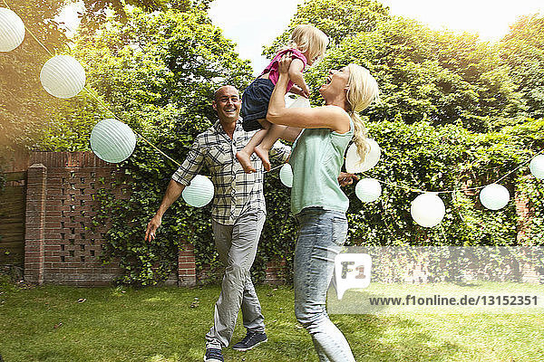 Happy couple playing with toddler daughter in garden