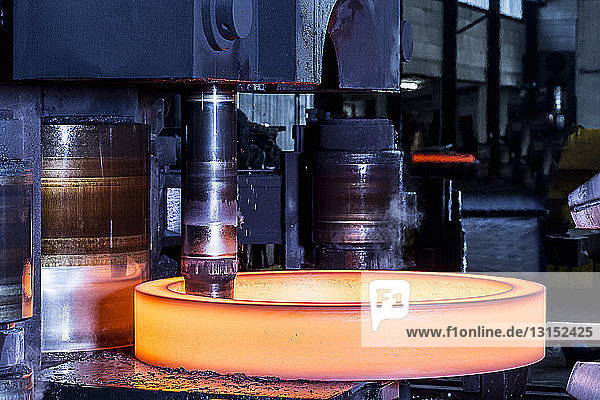 Close up of manufacturing machine shaping red hot steel ring in foundry