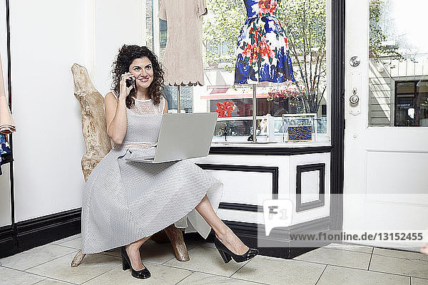 Portrait of mature woman sitting in fashion boutique  using laptop and smartphone