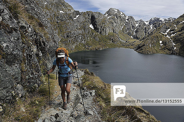 Woman hiking on path in mountains  New Zealand