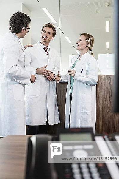 Three people wearing lab coats standing in office