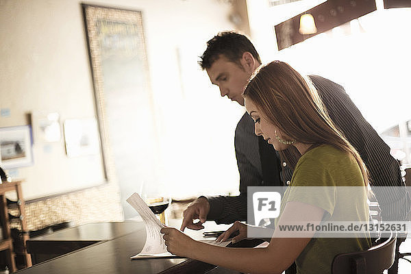 Business partners looking at paperwork in a wine bar
