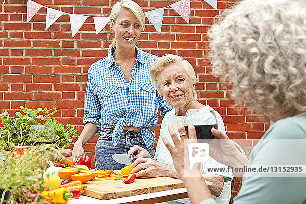 Three generation women chatting while preparing food at garden table