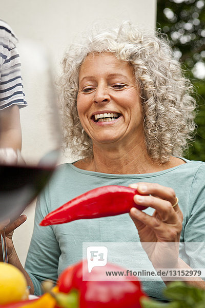 Mature woman holding a red pepper